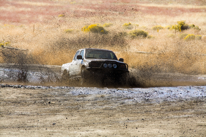 A truck driving through a puddle of mud